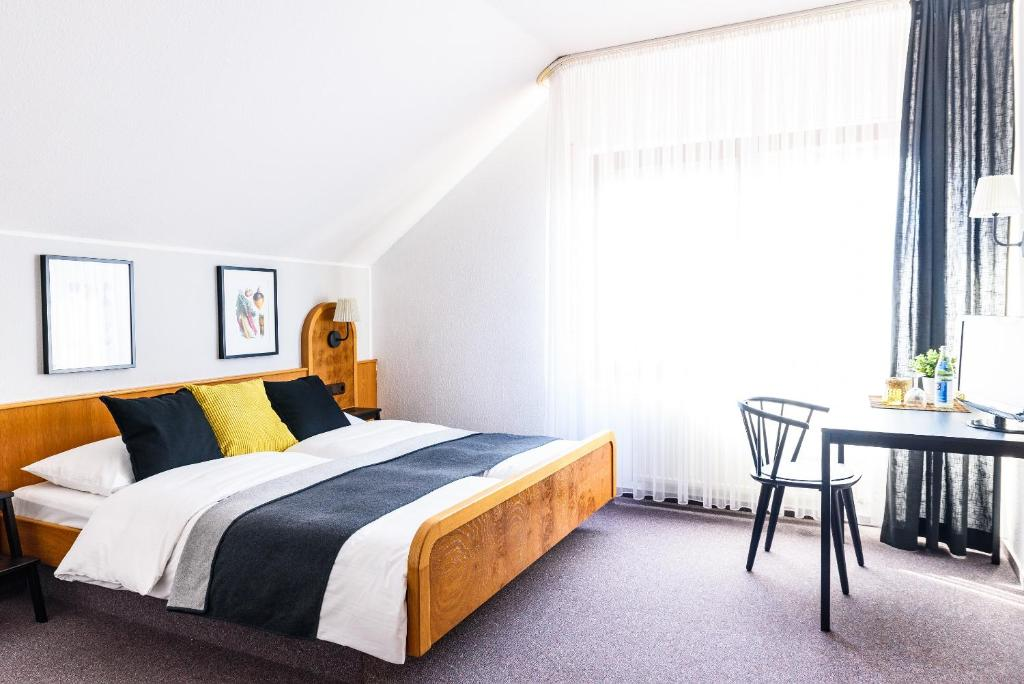 A bed or beds in a room at Landhotel Weingold Guntersblum