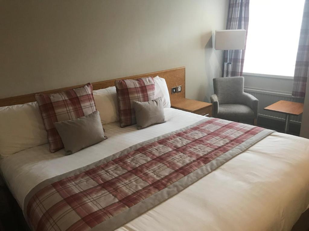 A bed or beds in a room at King Malcolm Hotel