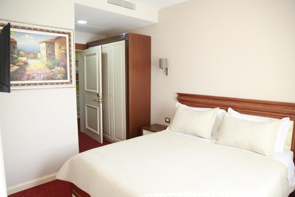 A bed or beds in a room at Rozafa Hotel