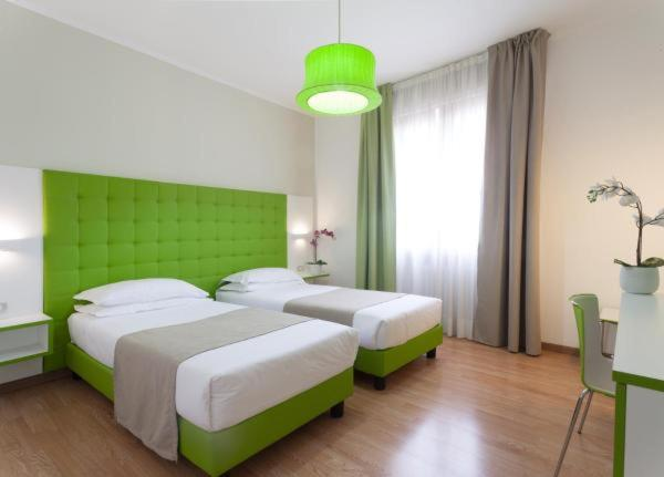 A bed or beds in a room at Hotel Milano Palmanova
