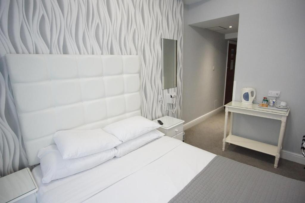 A bed or beds in a room at Swinton Hotel