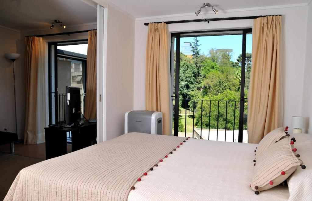 A bed or beds in a room at Lastarria Santiago Suite Apartments