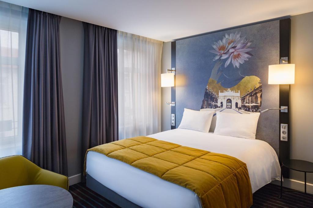 Een bed of bedden in een kamer bij Mercure Nancy Centre Place Stanislas