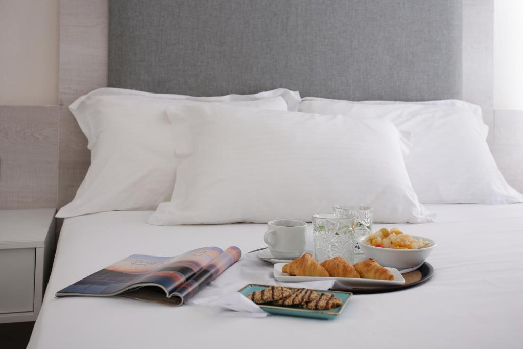 A bed or beds in a room at Studios Anny Family Hotel