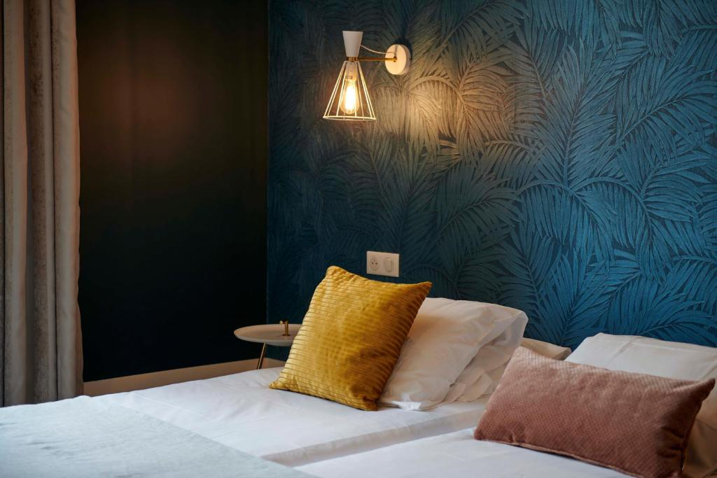 A bed or beds in a room at Hotel de France Restaurant Tast'vin