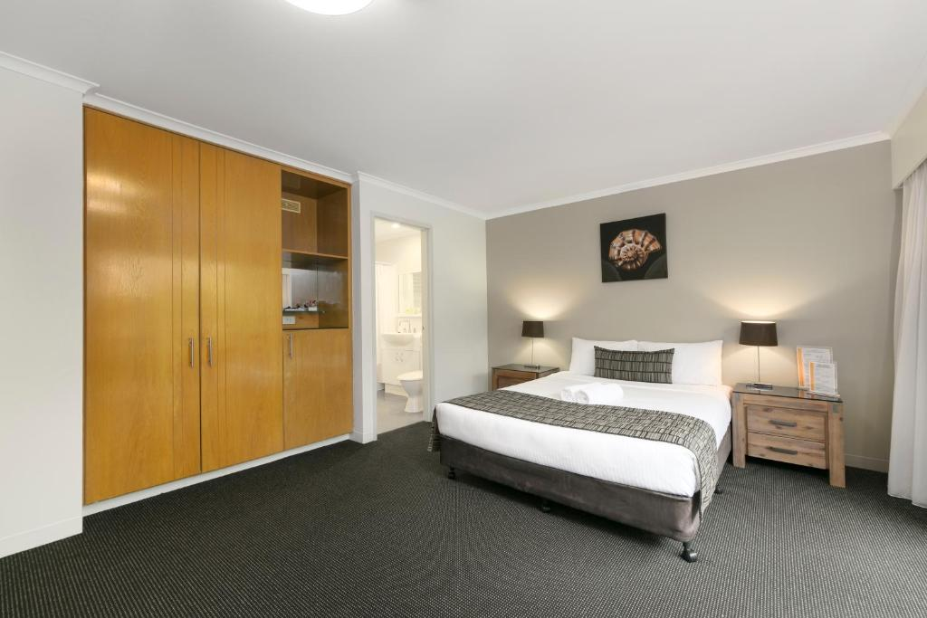 A bed or beds in a room at Mt Ommaney Hotel Apartments