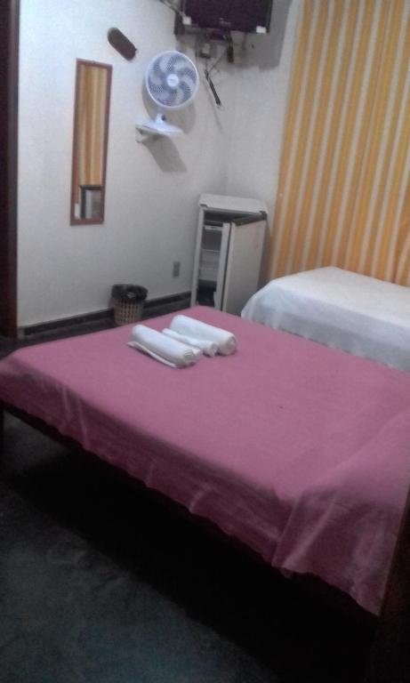 A bed or beds in a room at Pousada das Amendoeiras