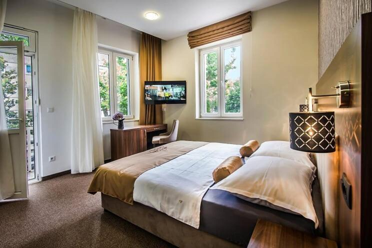 A bed or beds in a room at Central Luxury Rooms