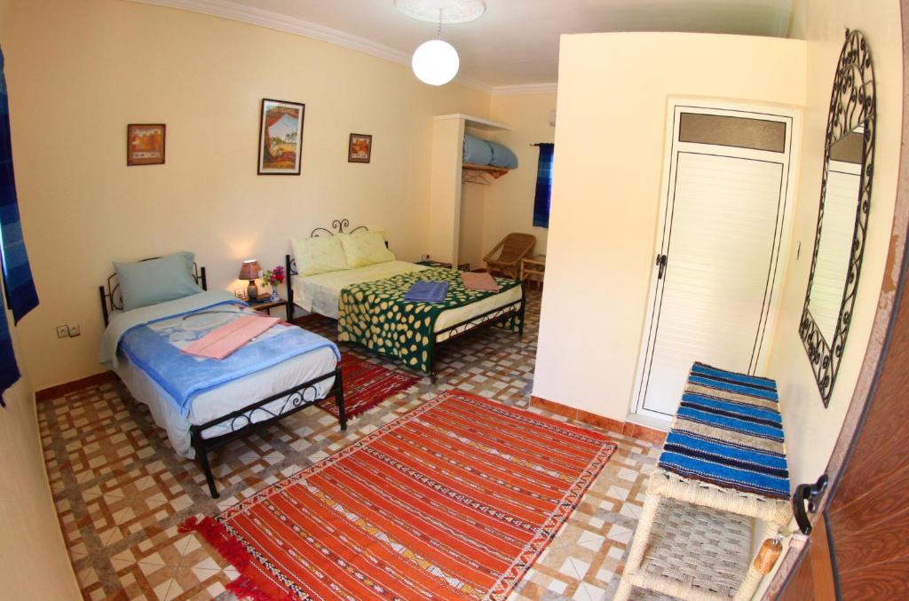 A bed or beds in a room at Palmeraie Guest House