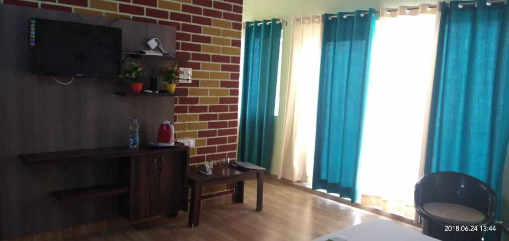 A television and/or entertainment center at Joshi Holidays Home Stay