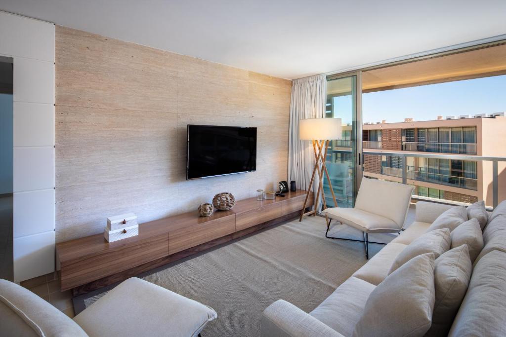 Una televisión o centro de entretenimiento en the Quest - Luxury Beach Apartment