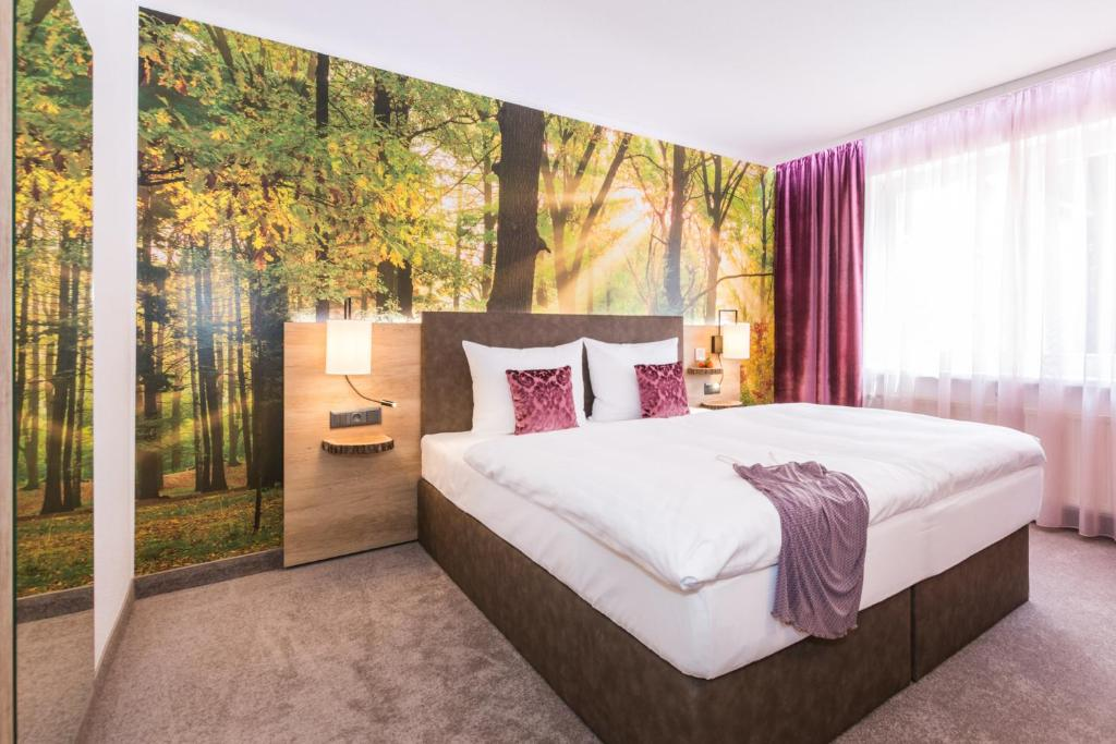 A bed or beds in a room at Trihotel - Wellnesshotel am Schweizer Wald