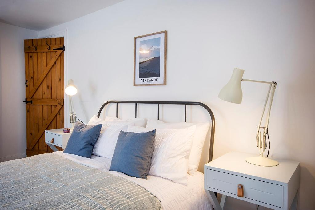 A bed or beds in a room at Cornish Cottage - Truro City Centre