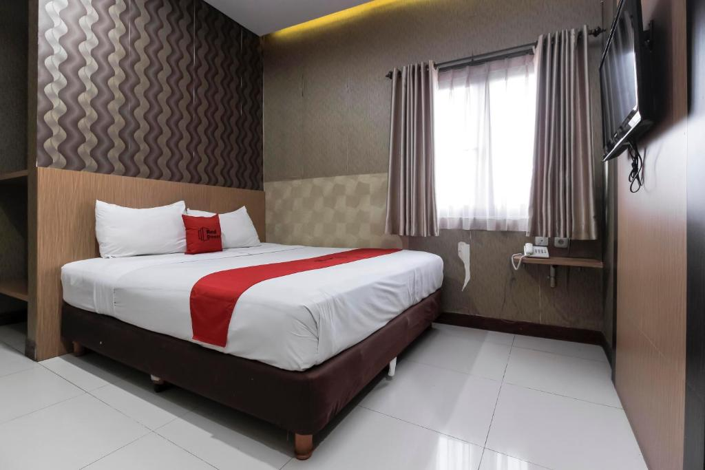 A bed or beds in a room at RedDoorz Plus @ Tuparev Cirebon