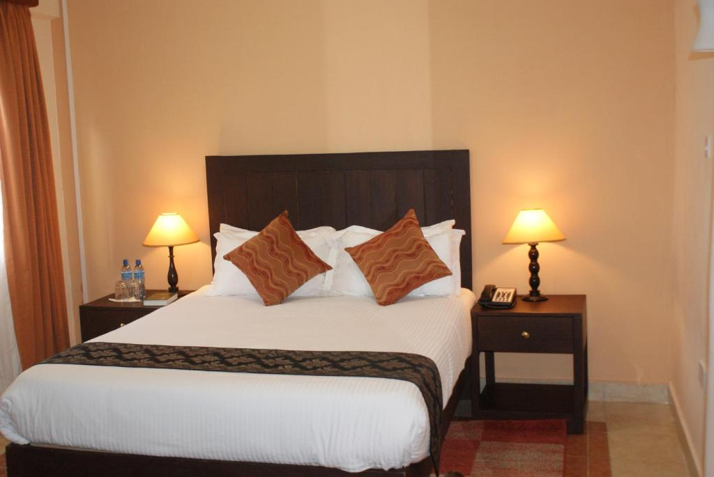 A bed or beds in a room at Nkubu Heritage Hotel
