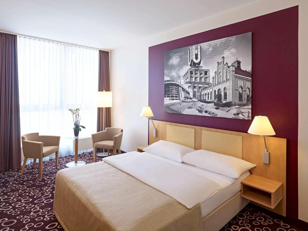 A bed or beds in a room at Mercure Hotel Dortmund City