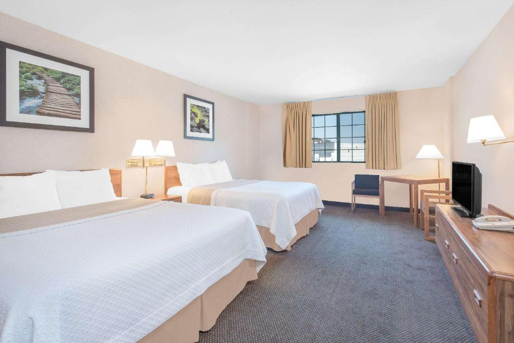 A bed or beds in a room at Days Inn by Wyndham West Rapid City