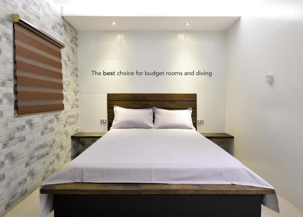 A bed or beds in a room at Habitat Guest House Sabang Puerto Galera