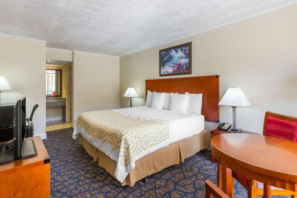 A bed or beds in a room at Days Inn & Suites by Wyndham Clermont