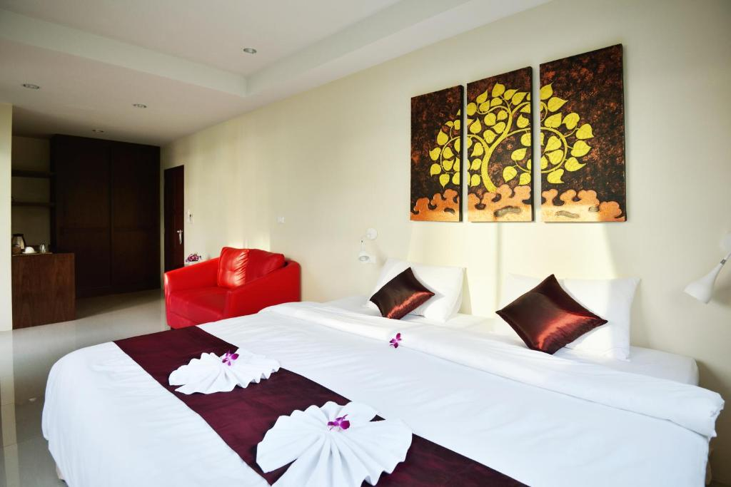 A bed or beds in a room at At Kamala Hotel