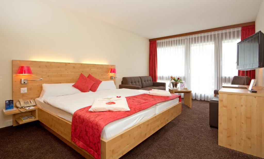A bed or beds in a room at Central Swiss Quality Sporthotel