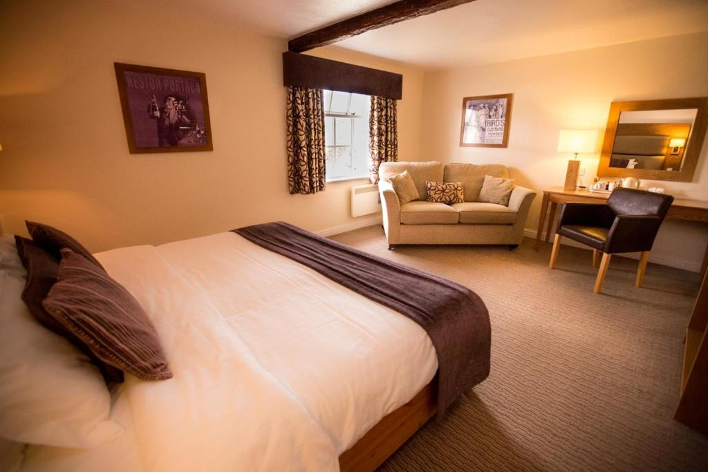 A bed or beds in a room at Guy's Thatched Hamlet