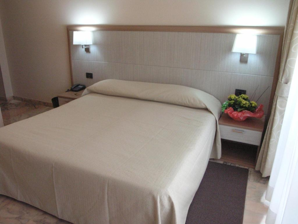 A bed or beds in a room at Hotel Smeraldo Torino