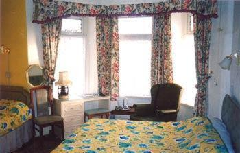 A bed or beds in a room at Southmead Guesthouse
