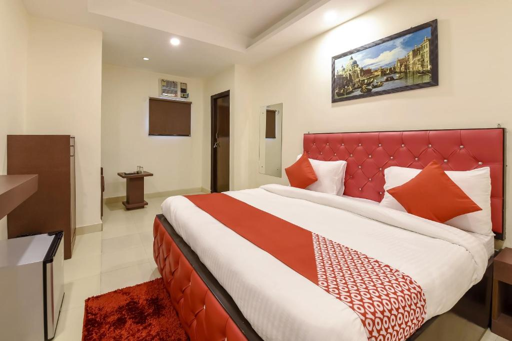 A bed or beds in a room at Capital O KH Hotel