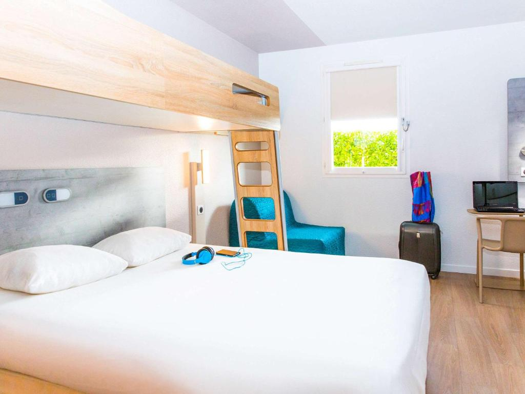 A bed or beds in a room at ibis budget Marmande
