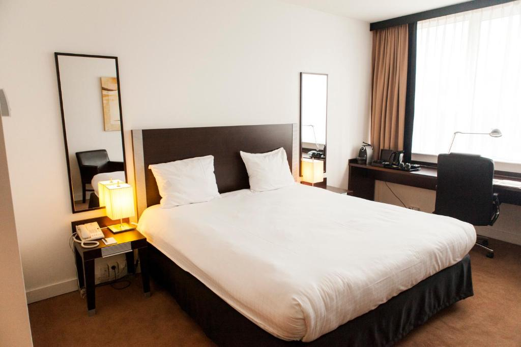 A bed or beds in a room at Progress Hotel