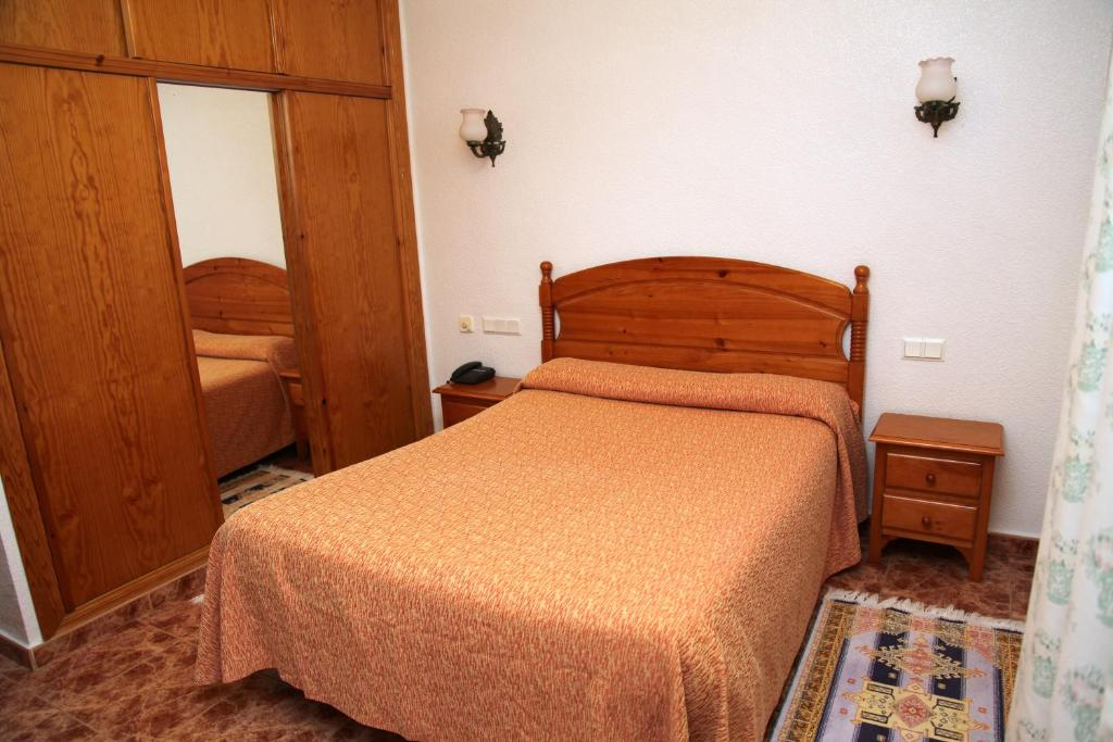 A bed or beds in a room at Hotel Los Arcos