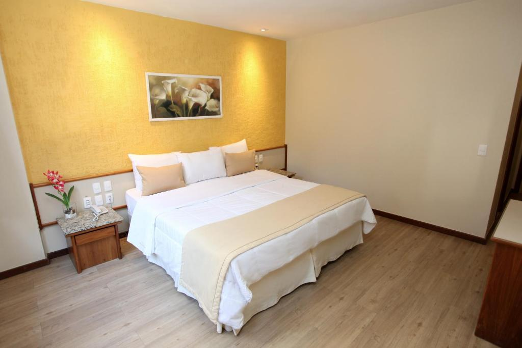 A bed or beds in a room at Mengo Palace Hotel