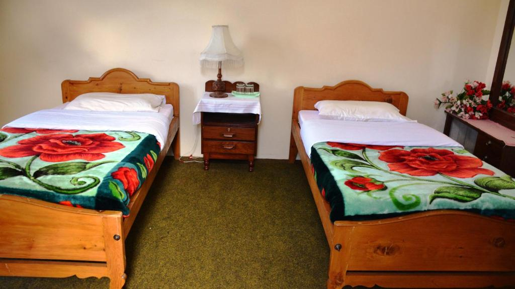 A bed or beds in a room at Gulmit Tourist Inn