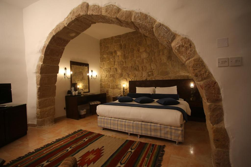 A bed or beds in a room at The Old Village Hotel & Resort