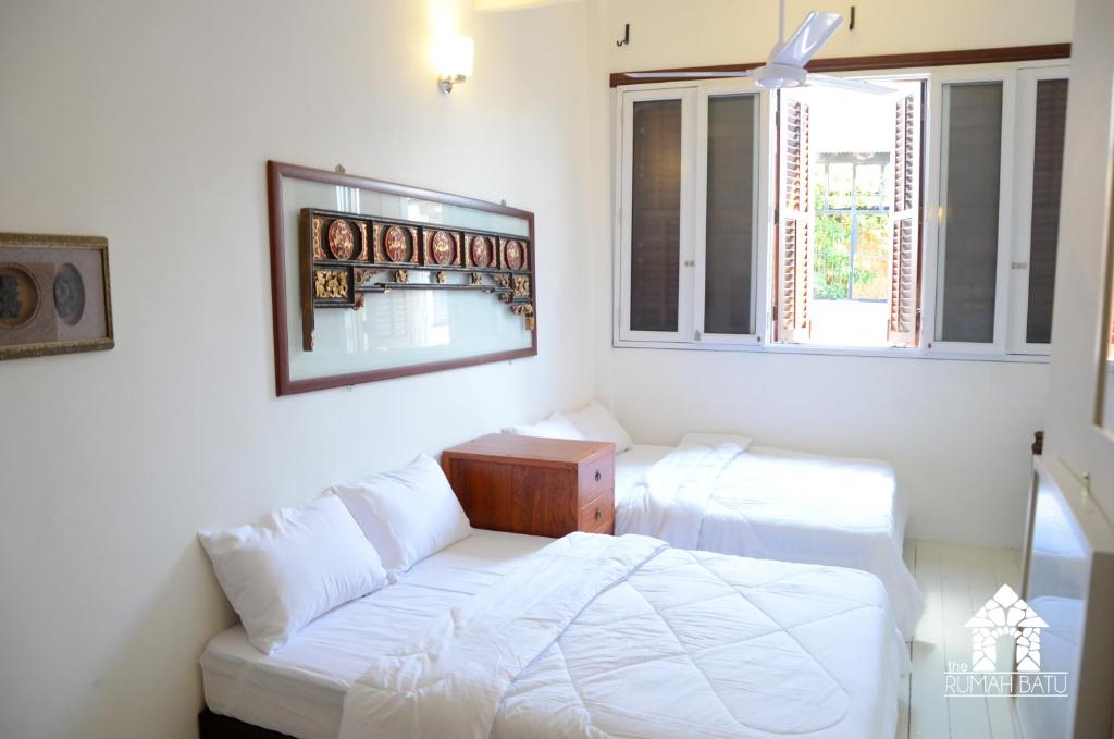A bed or beds in a room at The Rumah Batu Heritage