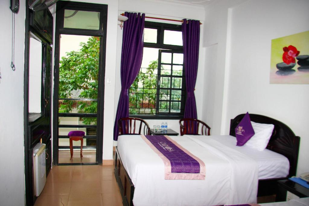 A bed or beds in a room at Carnosa Hotel Hue