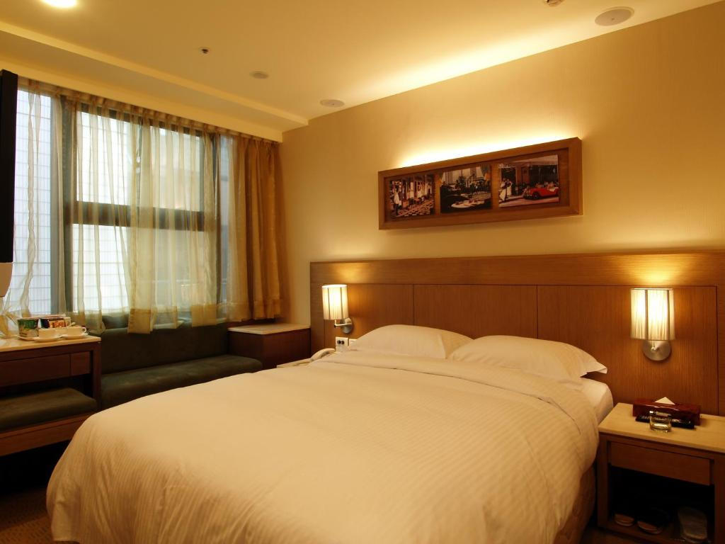 A bed or beds in a room at Eastern Star Hotel