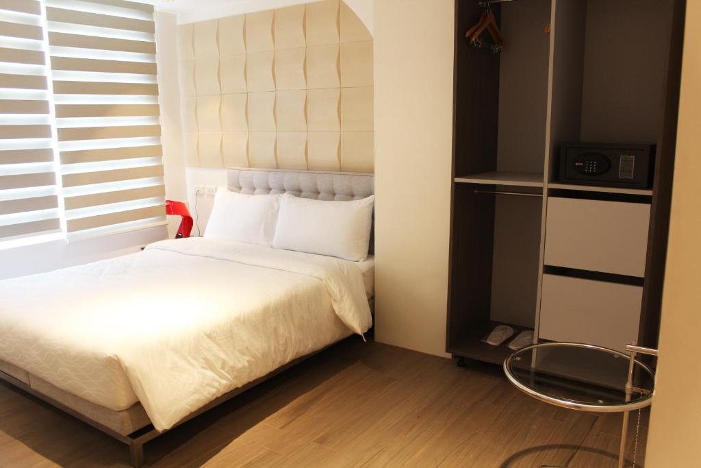 سرير أو أسرّة في غرفة في City Park Hotel Manila
