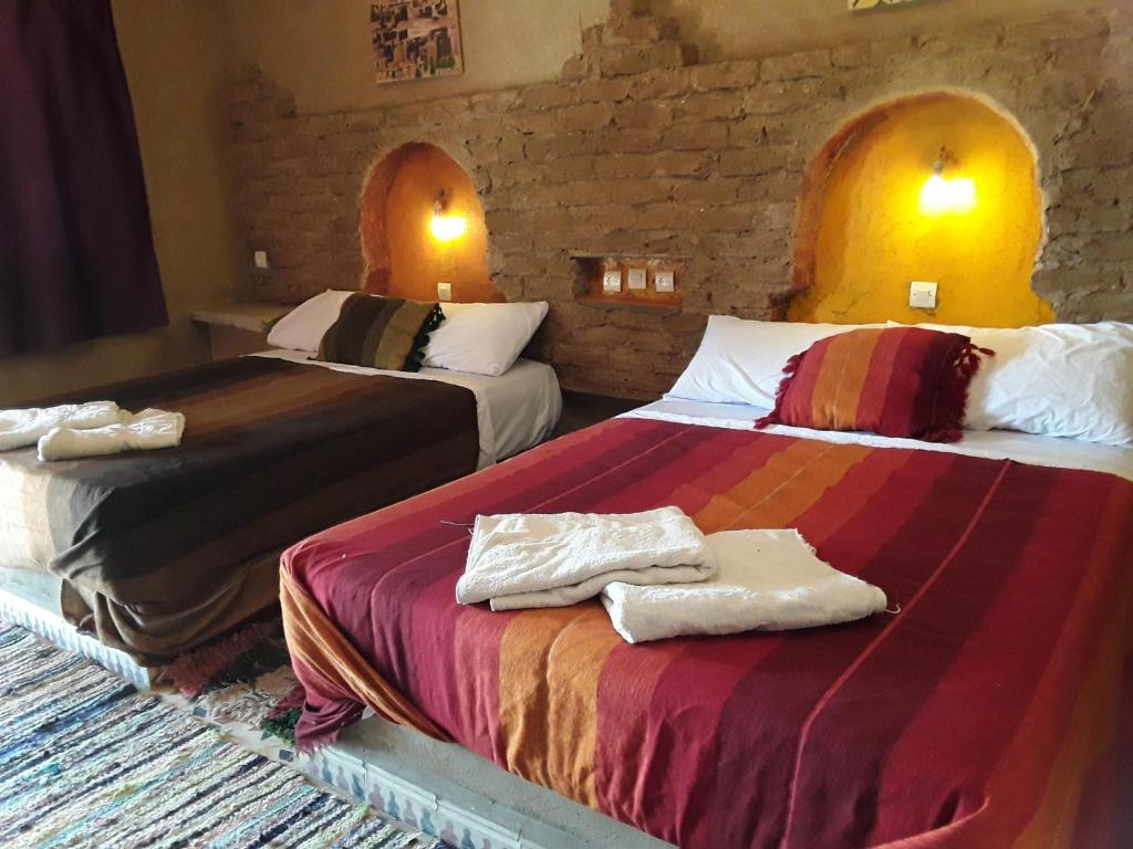 A bed or beds in a room at Auberge Camping La Liberté