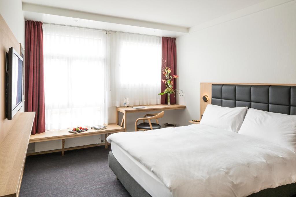 سرير أو أسرّة في غرفة في Hotel Basel - urbane Tradition und Moderne