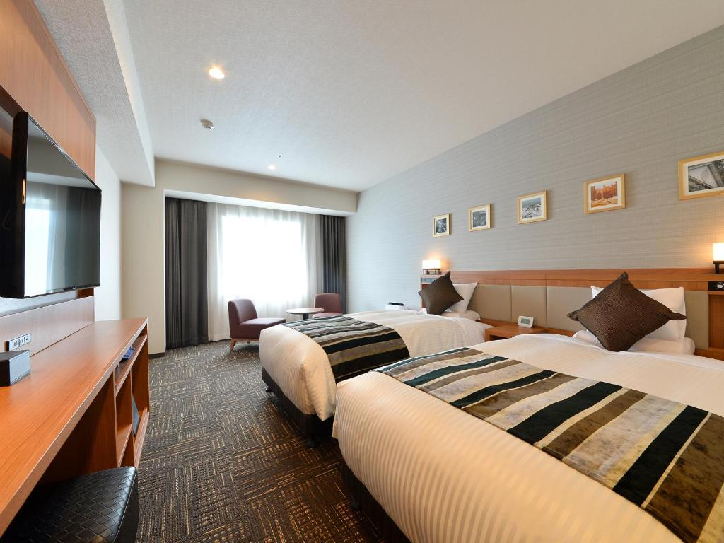 A bed or beds in a room at Hakodate Kokusai Hotel