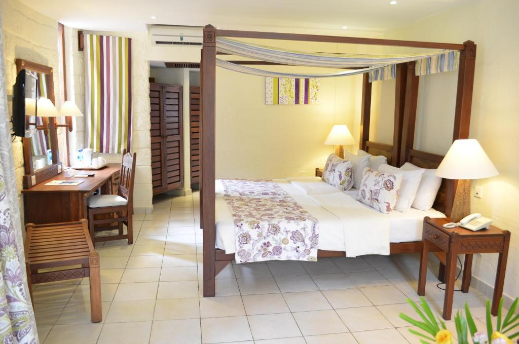 A bed or beds in a room at Baobab Beach Resort & Spa