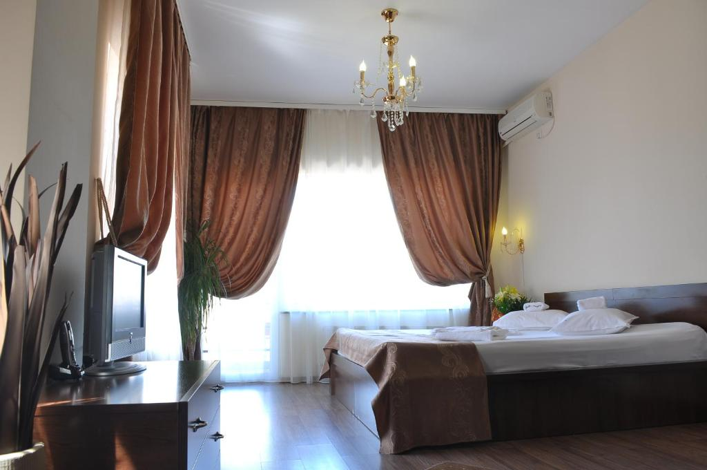 A bed or beds in a room at Ave Hotel Victoriei