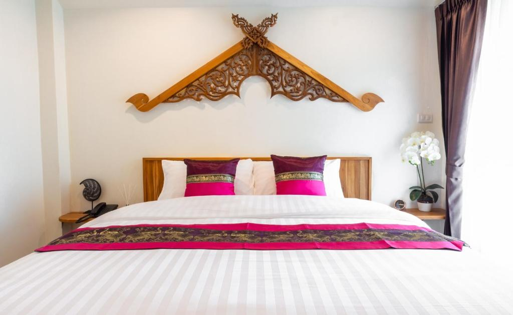 A bed or beds in a room at Anumat Premium Budget Hotel