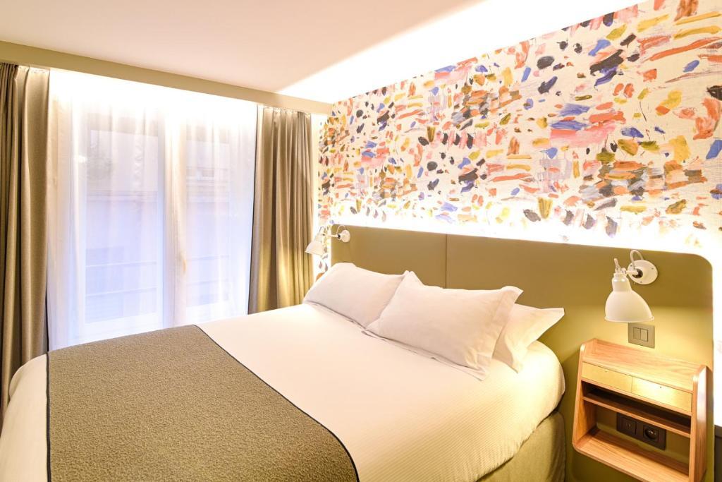 A bed or beds in a room at Hôtel Des Artistes
