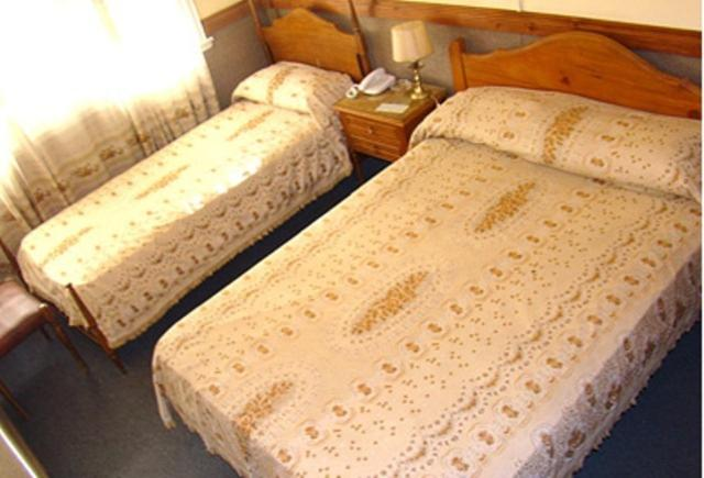 A bed or beds in a room at Hotel Austral