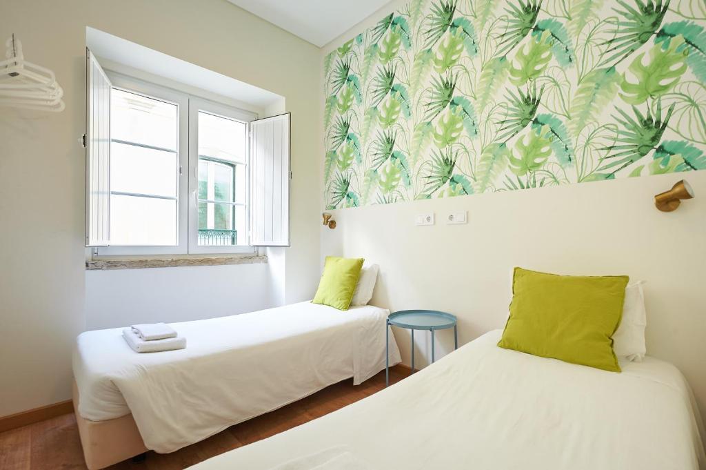 Een bed of bedden in een kamer bij Portugal Ways Santa Catarina Suites
