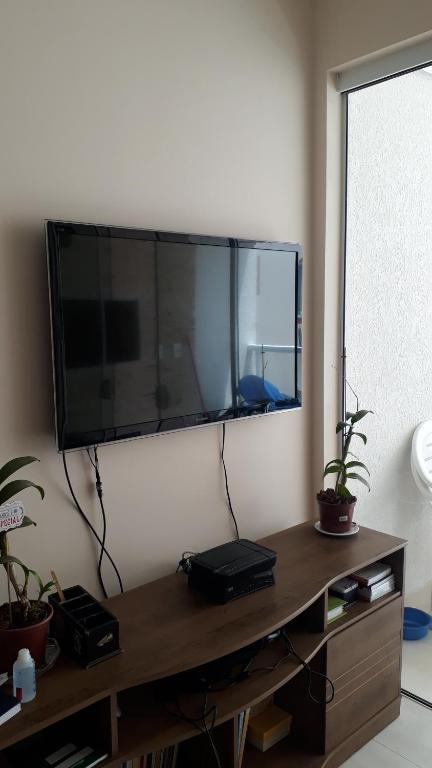 Una televisión o centro de entretenimiento en Excelente apartamento, 2 dormitórios, 200 m do mar
