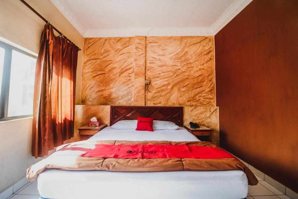 A bed or beds in a room at RedDoorz Plus near Jambi Prima Mall